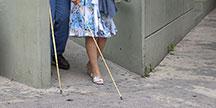 En blind person med vit käpp. Foto
