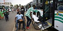 Personer i rullstol rullar in i en buss via en ramp. Foto