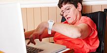 Funktionshindrad person som arbetar på en bärbar dator. Foto