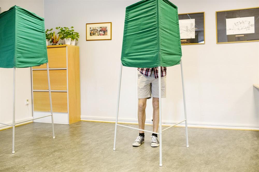 Man står bakom röstningsbås i vallokal. Foto: Per Hanstorp/Scandinav bildbyrå