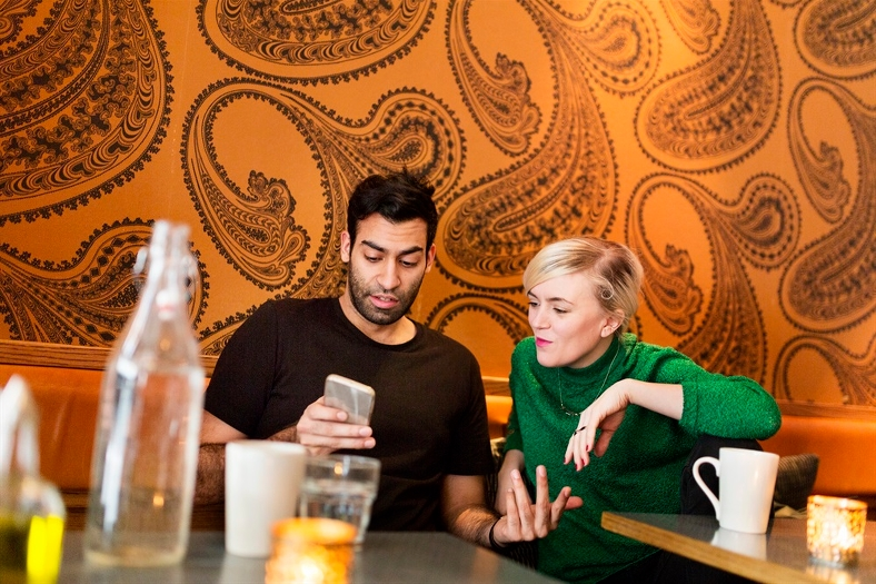 Man och kvinna tittar i mobiltelefon på kafé. Foto: Scandinav bildbyrå