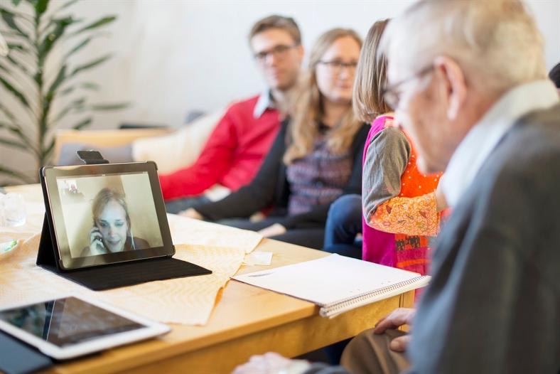 Äldre man talar med ung kvinna via telefon och webbkamera. Foto: David Zandén/Scandinav bildbyrå