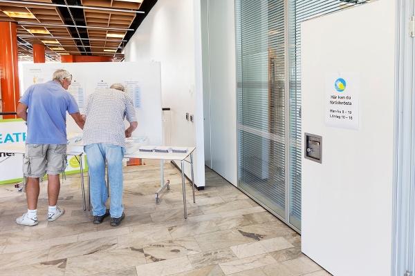 Två män placerar ut röstkort i vallokal. Foto: Marie Linnér/Scandinav bildbyrå