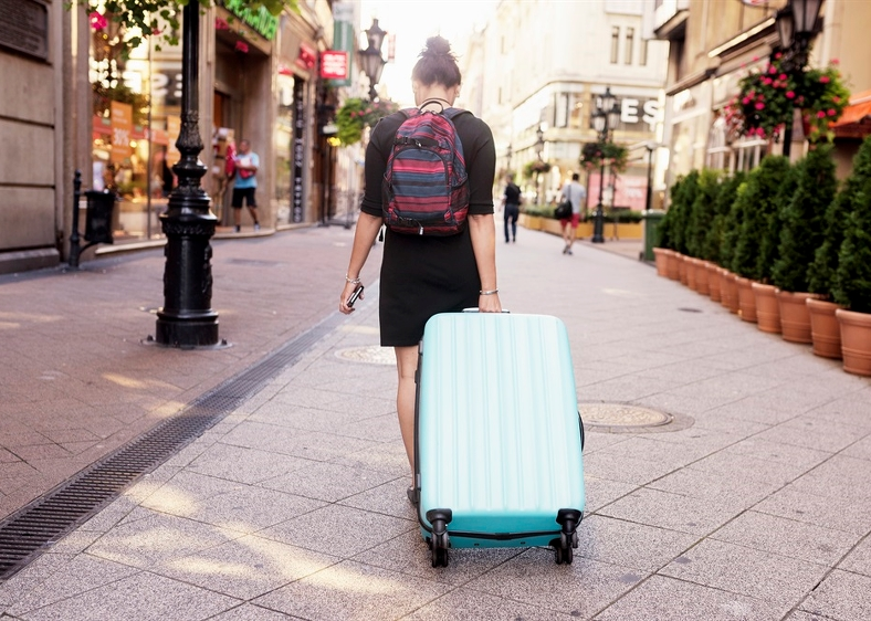 Ung kvinna på gågata med resväska. Foto: Jens Lindström/Scandinav bildbyrå