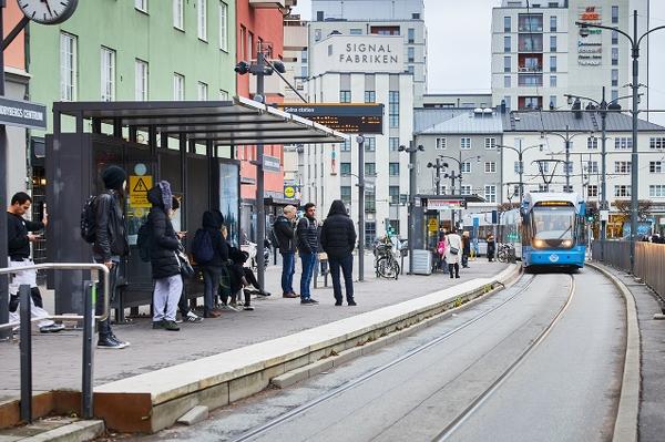 Gatubild med resenärer på perrong, väntande på en spårvagn. Foto: Pia Nordlander