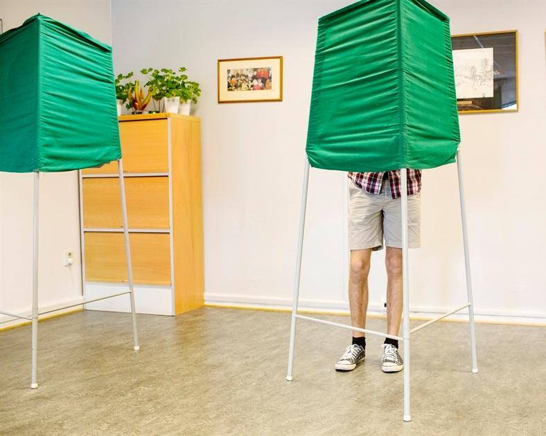 Valsedlar från olika politiska partier på ett bord, nedanför en tecknad symbol med person i rullstol.