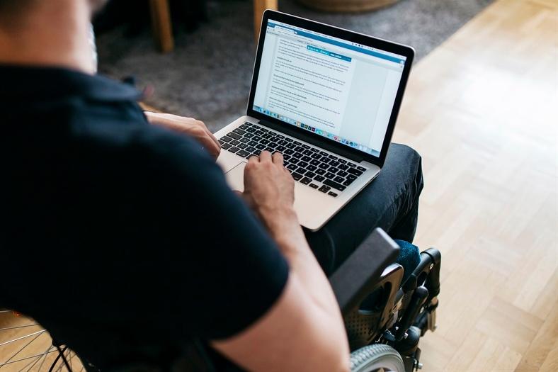 Man i rullstol med uppslagen laptop i knäet. Foto: Scandinav bildbyrå