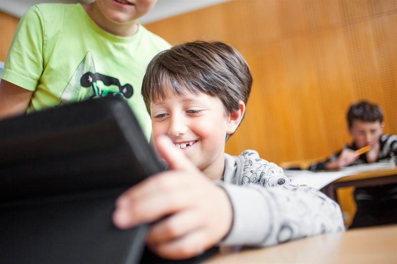 Leende pojke tittar på något på sin läsplatta i klassrummet. Foto: Astrakan/Scandinav bildbyrå
