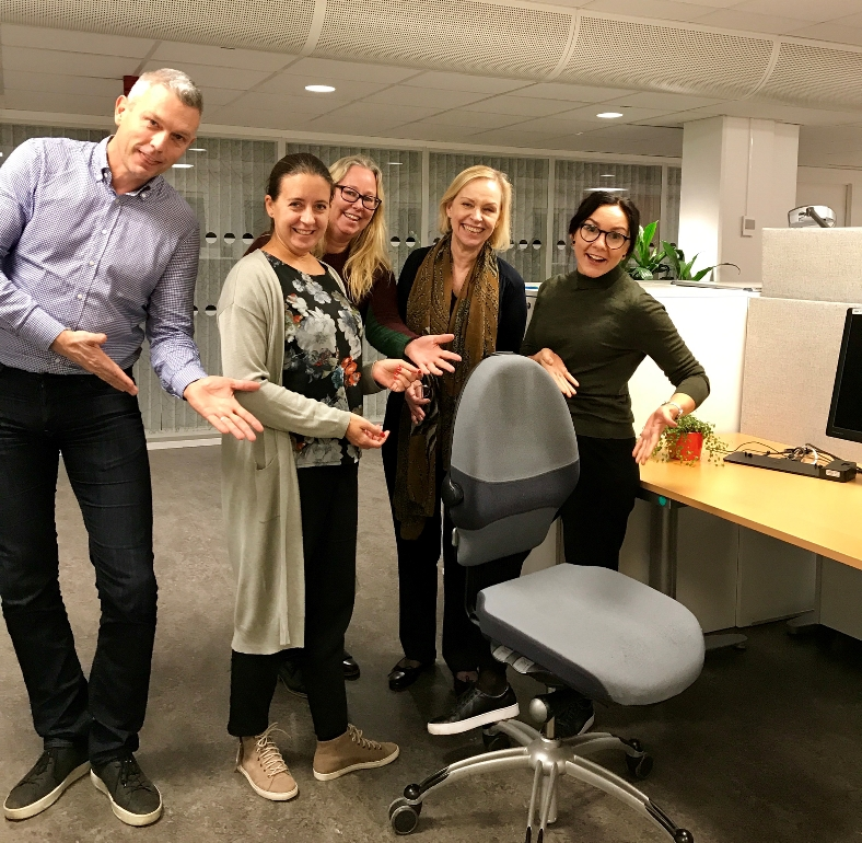 Fem medarbetare på MFD spexar bakom en tom kontorsstol på myndigheten. Foto: Anette Persson