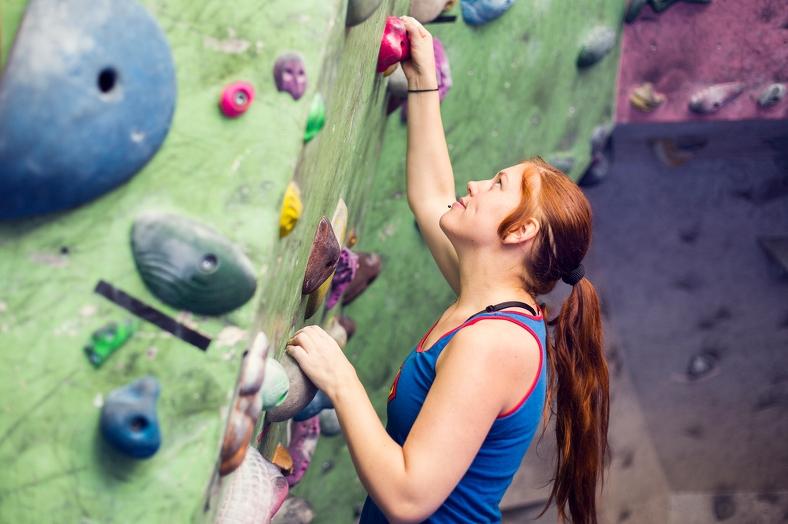 Ung kvinna med långt hår i hästsvans klättrar upp för klättervägg. Foto: Scandinav bildbyrå.