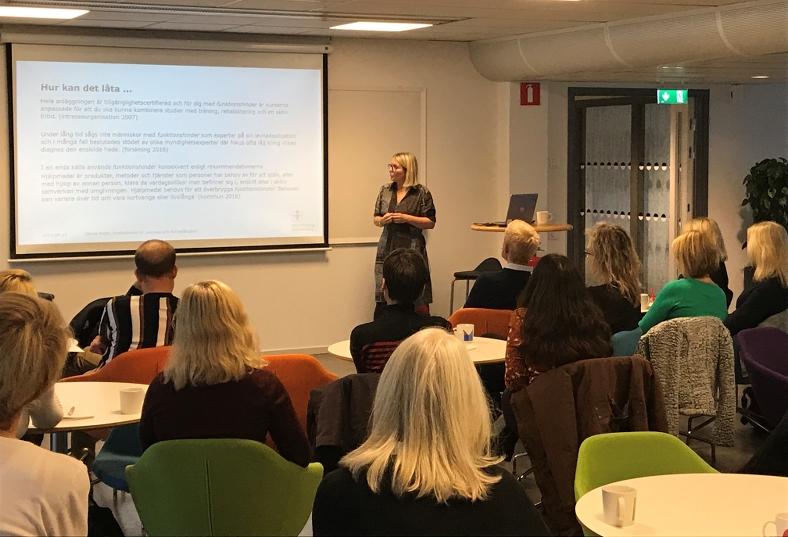 """Anna Vogel, forskare i nordiska språk, föreläser inför publik hos Myndigheten för delaktighet. Hon visar en bild på en skärm med en text som har rubriken """"Hur kan det låta..."""""""