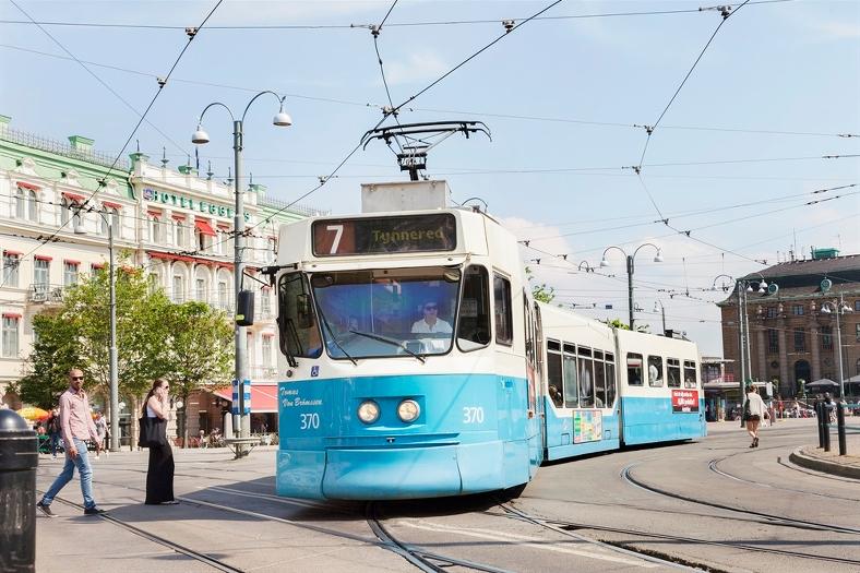 Blåvit spårvagn på väg genom ett soligt Göteborg.