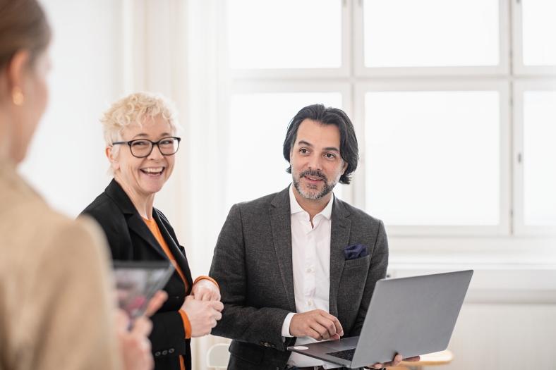 Två kvinnor och en man diskuterar något framför en uppfälld bärbar dator. Foto: Scandinav bildbyrå.