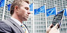 An EU building and a man using a tablet. Photo