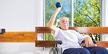 An older man exercises and lifts weights. Photo